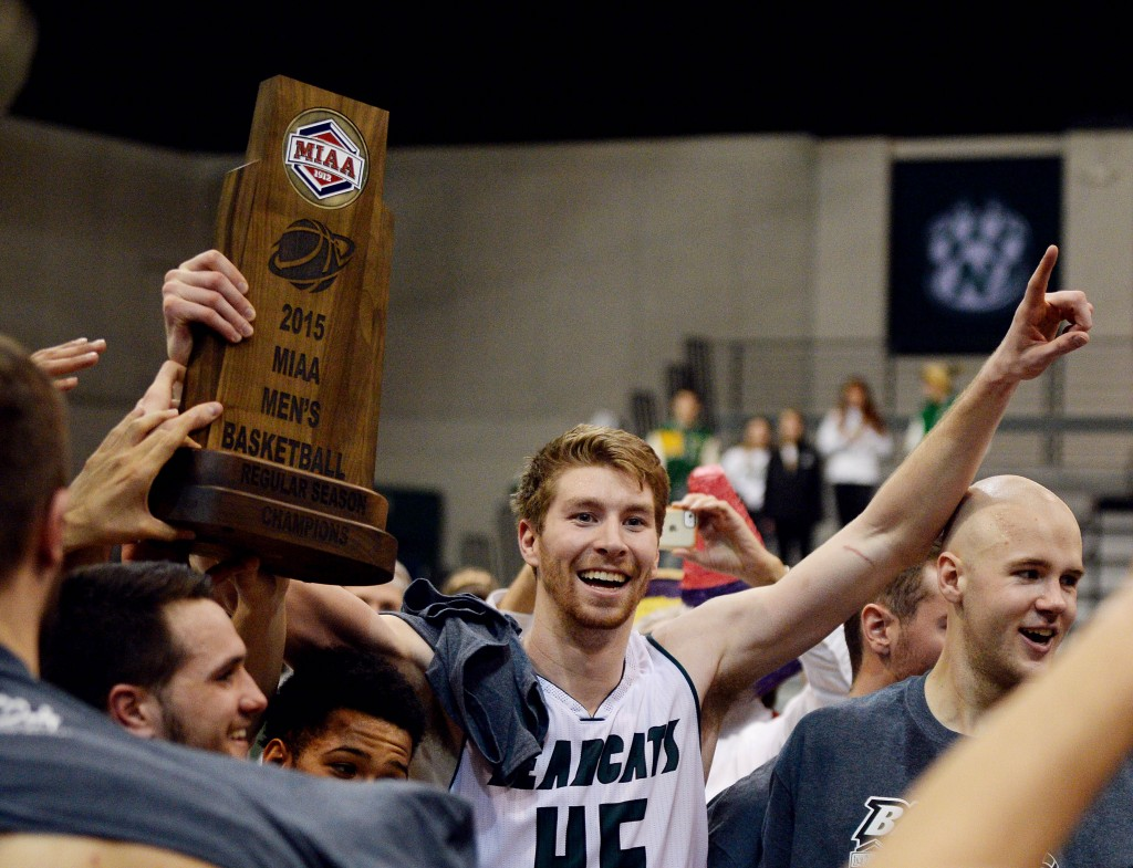 Northwest Missouri State center Grant Cozad holds the 2015 MIAA Men's Basketball Regular Season Championship trophy concluding a 83-73 victory over Central Missouri.