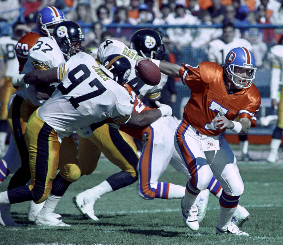 Denver Broncos quarterback scrambles out of the pocket against Pittsburgh at Mile High Stadium.