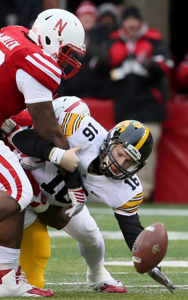 Nebraska defensive end Greg McMullen strips  the ball  from Iowa quarterback C.J. Beathard during first half action at Memorial Stadium in Lincoln.