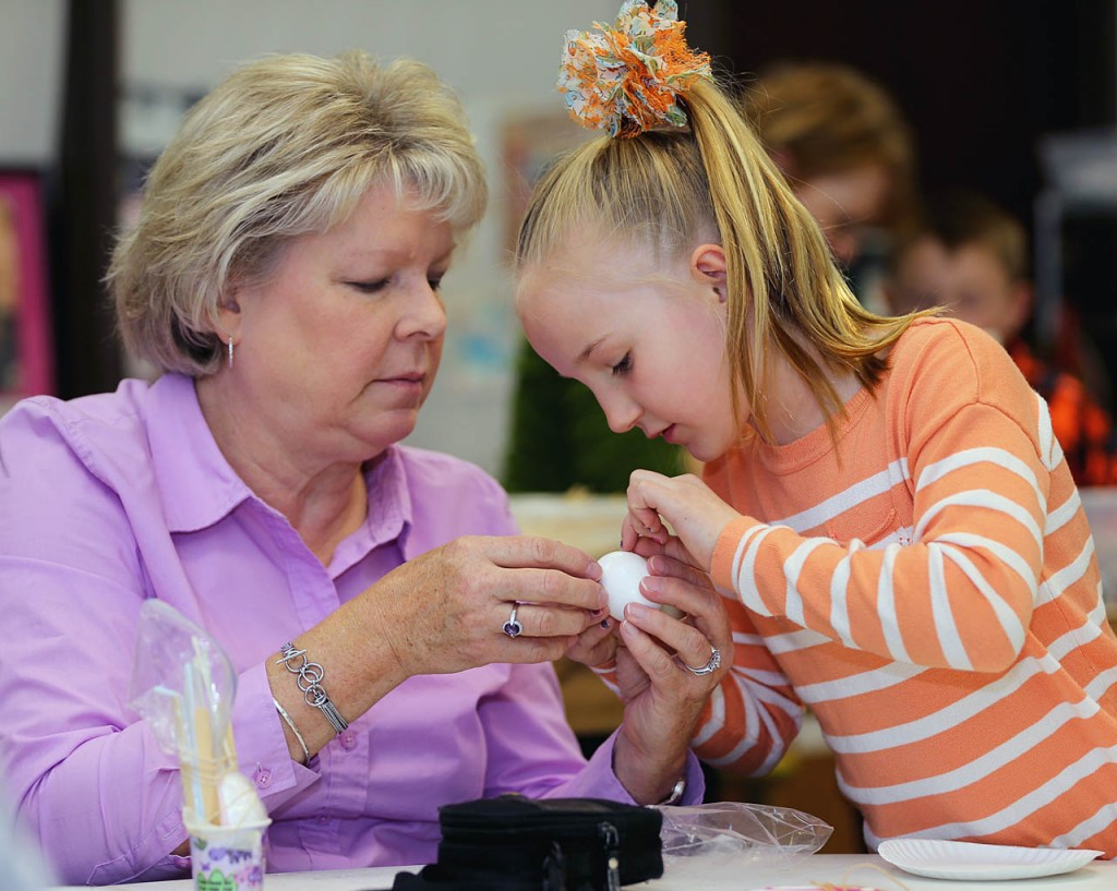 Kris Yockey, left, helps her granddaughter Micole with preparing an egg for a drop from the Edgerton Explorit Center rooftop during Easter Eggstravaganza in Aurora, Neb.
