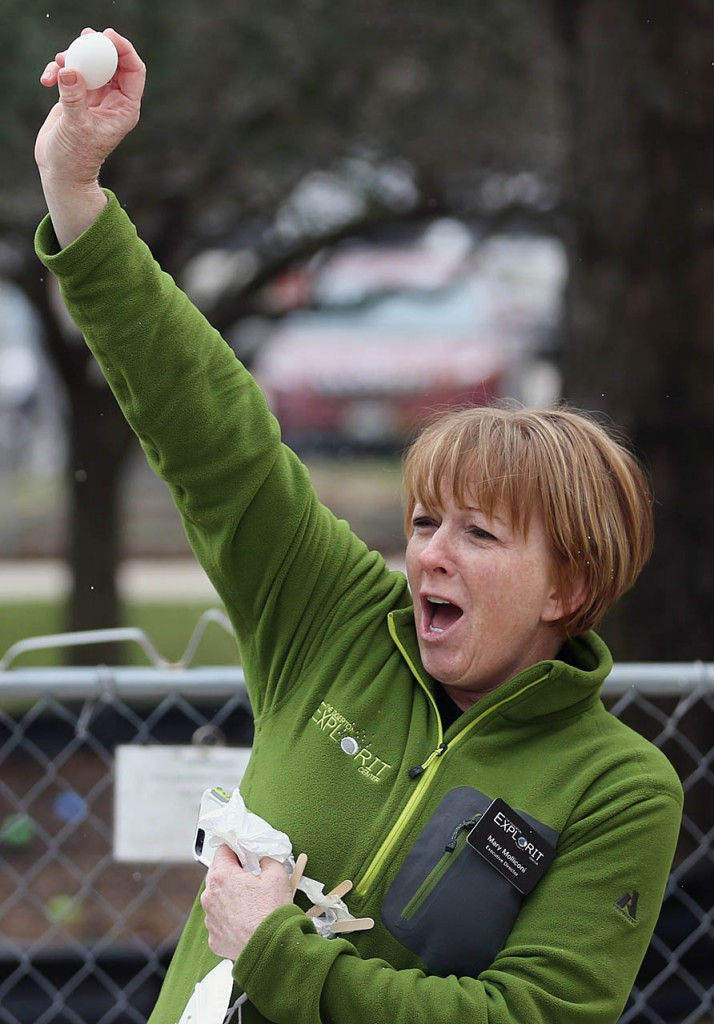 Mary Molliconi, executive director of The Edgerton Explorit Center holds up Tyson Dvorak's egg which was the first of three eggs to survive the egg drop at Easter Eggstravaganza in Aurora, Neb.
