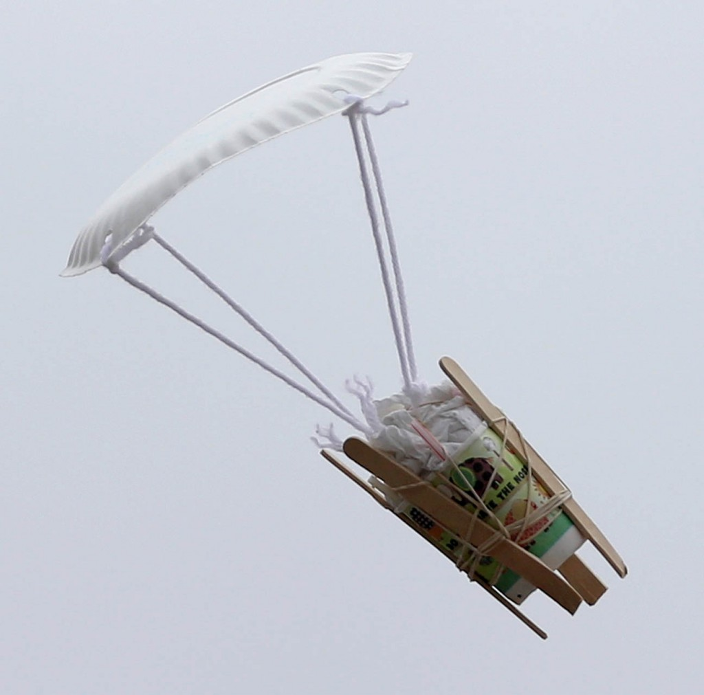 An egg wrapped up in a paper towel inside a dixi cup with tongue depressers and a paper plate parachute desends from a rooftop during an egg drop contest.