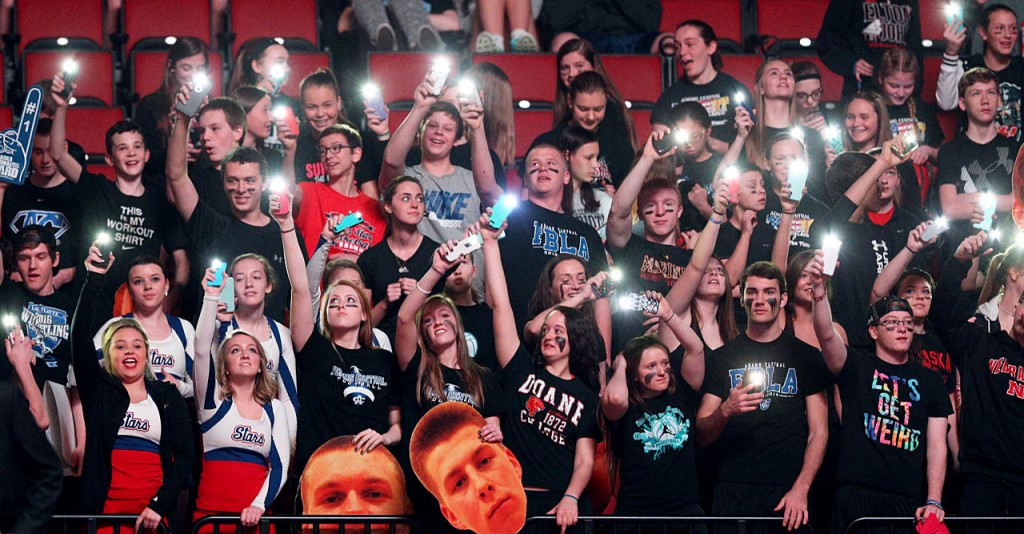 The arena lights are turned off as part of a pregame effect and Adams Central students use their cell phones to illuminate the darkness during the NSAA State Boys Basketball Championship game against Bishop Neumann at the Pinnacle Bank Arena Saturday. Bishop Neumann won 63-54.