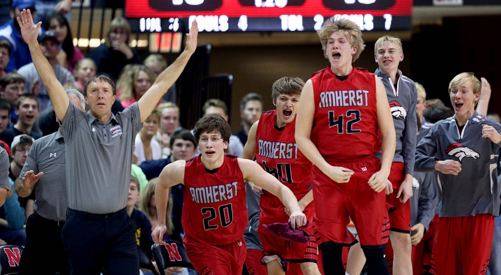 The Amherst bench erupts as they battle St. Francis late in the fourth quarter.