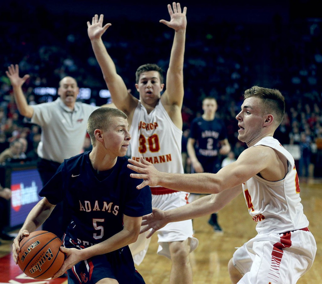 Adams Central senior Garrett Sittner (5) is guarded by Bishop Neumann's Theodore Blum (30) and Benjamin Simons during the NSAA State Boys Basketball Championships finals at the Pinnacle Bank Arena Saturday. Bishop Neumann head coach Mike Weiss is yelling out. Bishop Neumann won 63-54.