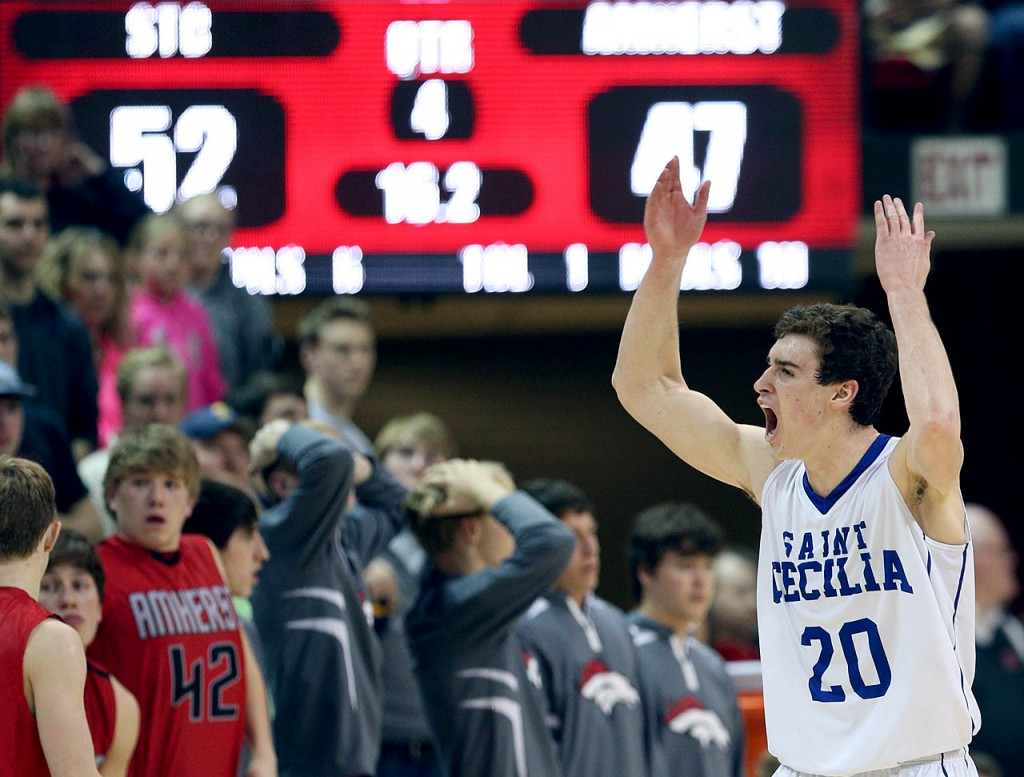 Hastings St. Cecilia senior Zachary Kitten fires up Bluehawks fans during a timeout against Amherst during the NSAA State Boys Basketball Championships at the Bob Devaney Sports Complex Friday. Hastings St. Cecilia won in overtime 53-47.