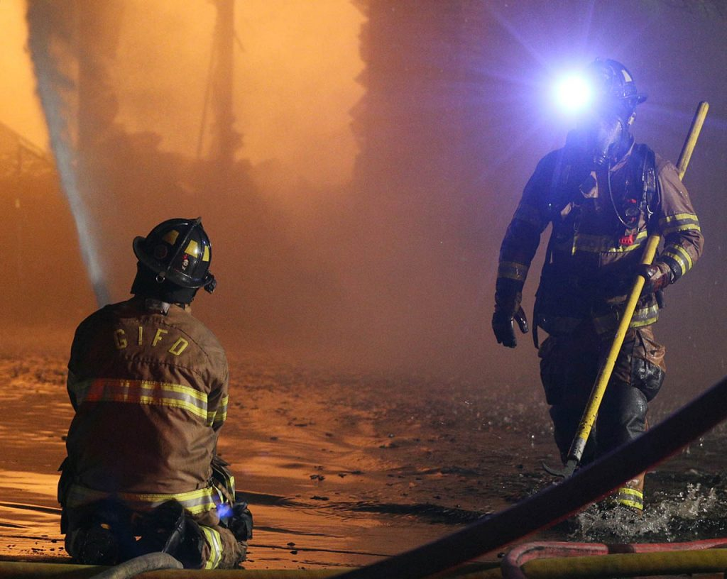 A Grand Island firefighter takes a low angle with a fire hose, left, to spray directly onto a structure fire right after windows were knocked out as crews battle an overnight blaze at 808 W. North Front St. Sunday.