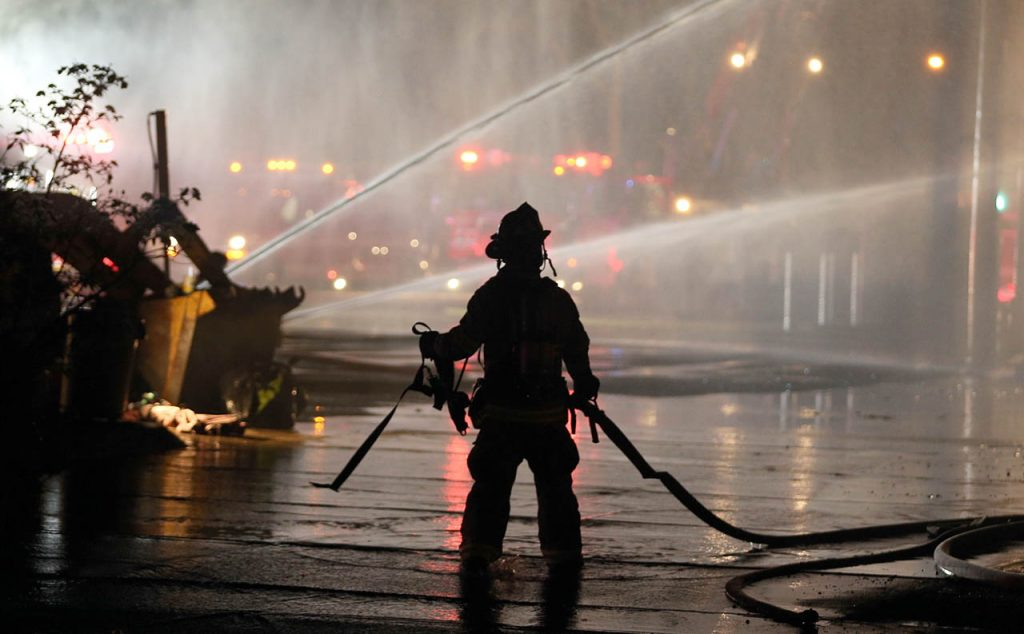 A Grand Island firefighter walk with a fire hose as water cascades from other hoses used to battle an overnight fire atr 808 W. North Front St.