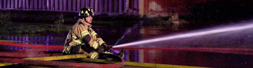 A Grand Island firefighter sits on a fire hose to control it's powerful pressure while directing it at a structure fire at 808 W. North Front St. Sunday.