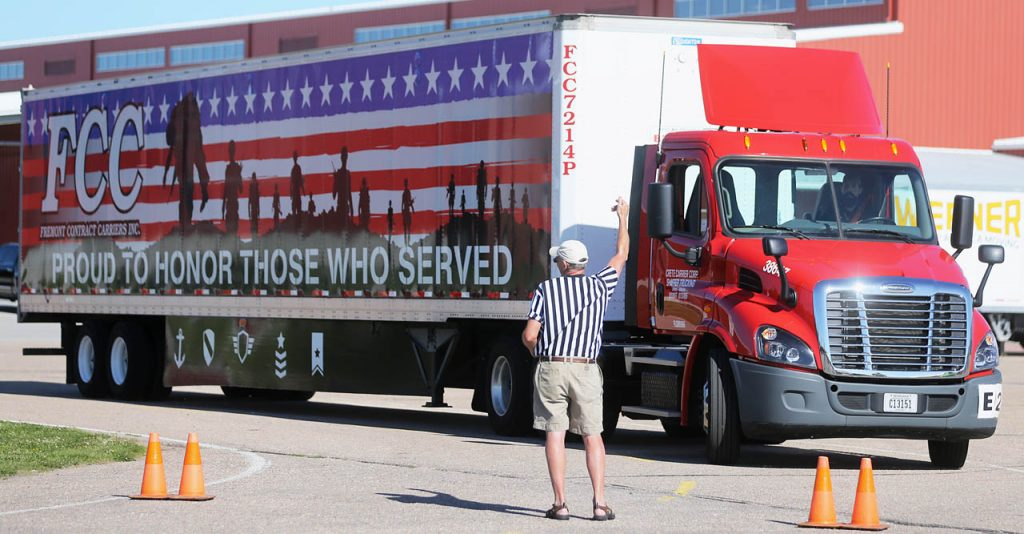 Alan Rogers, safety director with Wynne Transport Service, motions for driver Joe Busch to come up to the starting line during the Nebraska Truck Driving Championships at Fonner Park Saturday. Ninety-eight drivers competed in six stations that are simulated challenges drivers face every day.