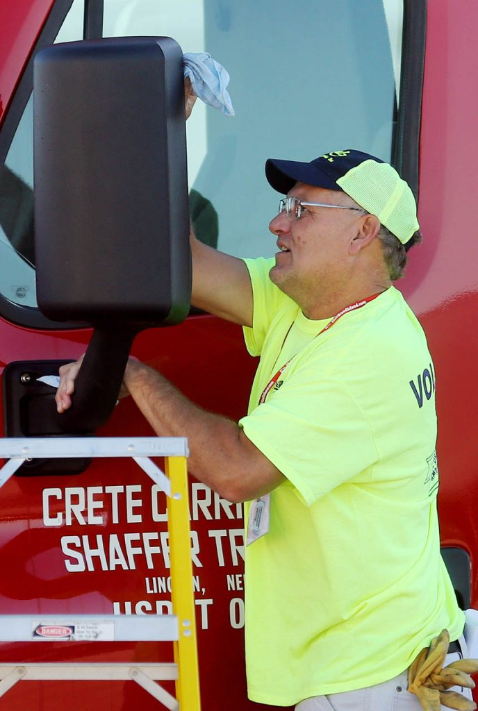 John Dostal with Schulz Transportation Services cleans a side mirror of a semi parked in the pre-stage area during the Nebraska Truck Driving Championships at Fonner Park Saturday. (Independent/Andrew Carpenean)