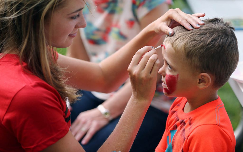 Madison Erickson paints Brady Smith's of Hastings face to look like Spiderman during A'ROR'N Days Thursday night in Aurora, Neb.