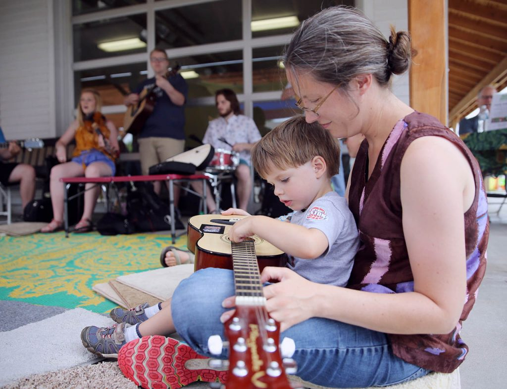 Oliver Nyman learns to play a ukulele while sitting on his mothers lap Amanda Solem of Hastings during an instrument petting zoo at The Flatwater Music Festival Saturday. The Wildwoods Band plays in the background. (Independent/Andrew Carpenean)