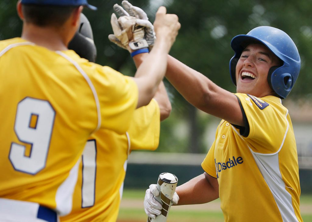 Tom Dinsdale's Jarod Kolar, right, celebrates with teammates after scoring a run against First Nationals of North Platte at Ryder Park Friday. (Independent/Andrew Carpenean)