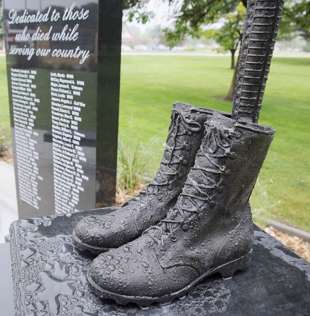 Rain beads up on combat boots which is part of the Heartland Veterans Memorial in Central City. Steady rain showers forced the memorial dedication to take place inside the Performing Arts Center Saturday.