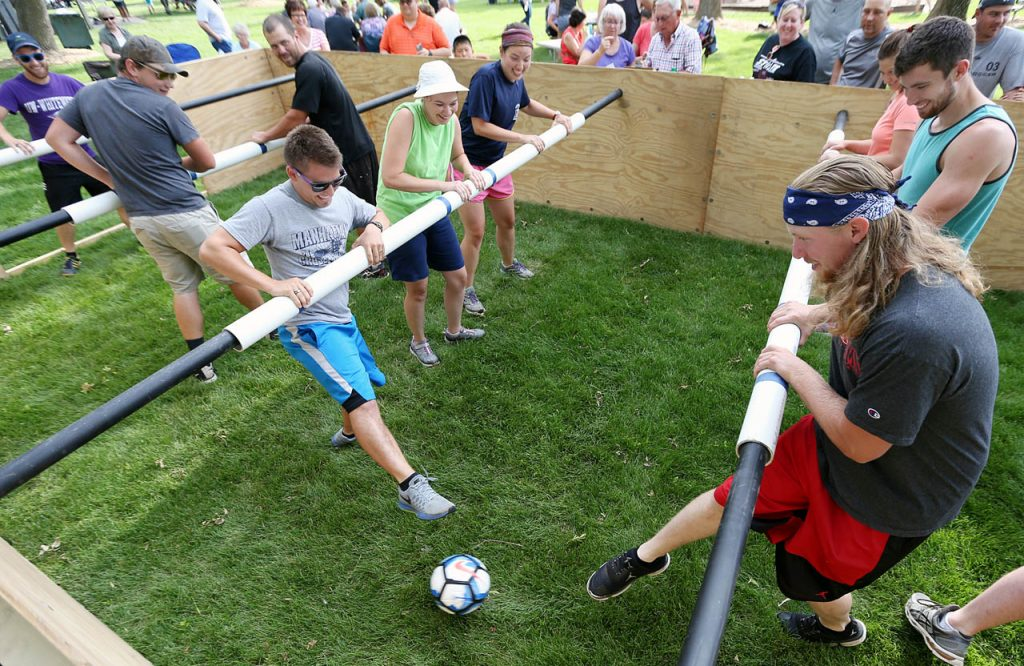 Spencer Friesen, right, kicks the ball during a game of human foosball at Henderson Community Days.
