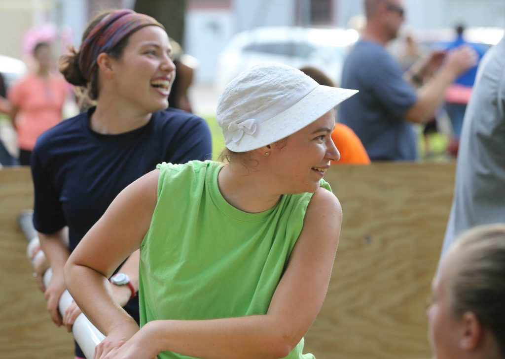 Becca Page, left, and Brianna Bartholomew share a laugh while playing a game of human foosball at Henderson Community Days.