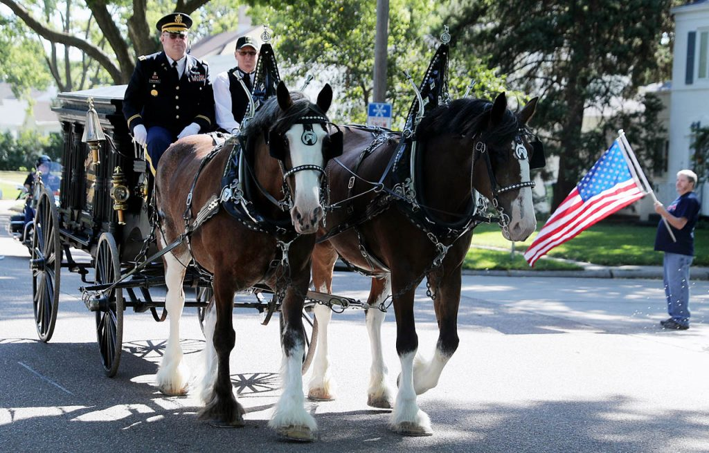 Chaplin Richard Piontkowski rides next to Brent Jorgensen as he drives two Clydesdales down W. Koenig St. with the body of Marine Pvt. Dale R. Geddes in an original 1872 horse-drawn hearse Monday, August 22, 2016 in Grand Island, Neb. Geddes remains were identified after being discovered 72 years after being killed in the Battle of Tarawa during World War II. The precession started at Apfel Funeral Home with a final resting place at Grand Island City Cemetery. Art Anson, who's father Bernard Hanson was a WW II veteran holds a flag as the hearse passes. (Andrew Carpenean/The Independent via AP)