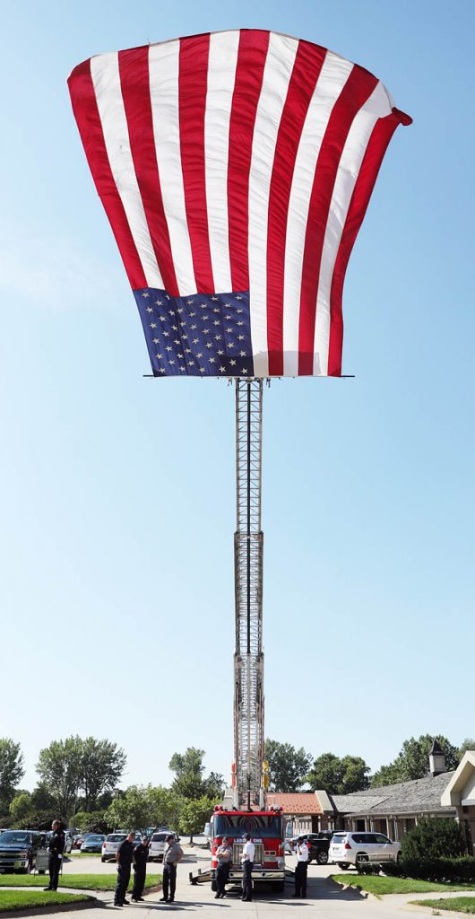 The Grand Island Fire Dept. flies a flag from the top of a ladder engine in honor of Marine Pvt. Dale R. Geddes on the funeral procession on Stolley Park Rd. Monday, Aug. 22, 2016 in Grand Island, Neb. (Andrew Carpenean/The Independent via AP)