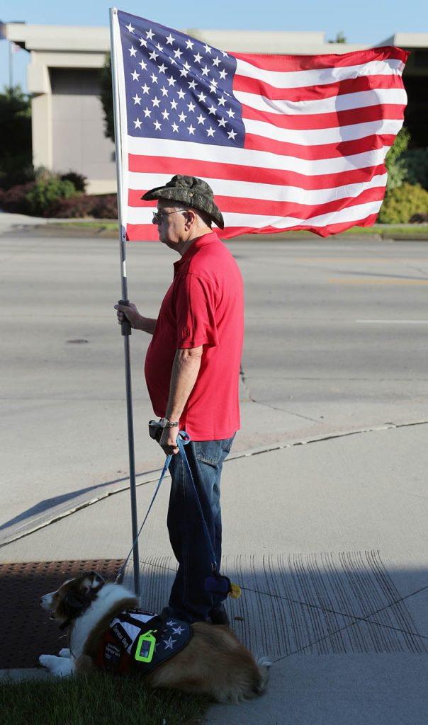 Dave Davis, a Vietnam Veteran, and his service dog Dakota stand outside Apfel Funeral Home as Davis posts an American flag in honor of Marine Pvt. Dale R. Geddes Monday. (Independent/Andrew Carpenean)