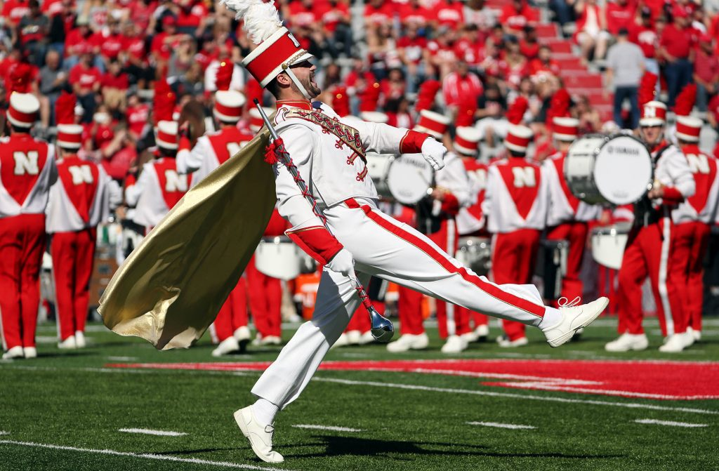 The one out front a University of Nebraska Cornhusker Marching Band drum major performs as the band takes the field prior to the Wyoming Cowboys vs. Nebraska Cornhuskers NCAA football game at Memorial Stadium in Lincoln.