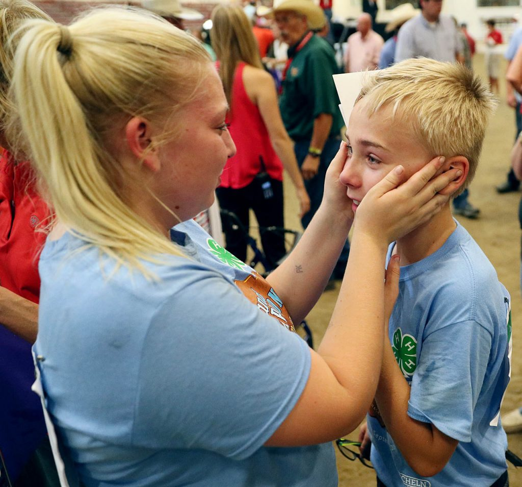 Bruren Strope of O'Neil, Neb., left, reaches out to his sister Tejlor who just won the 4-H Market Beef Grand Champion for showing Paddy at the Five points Bank Arena on Labor Day Monday.