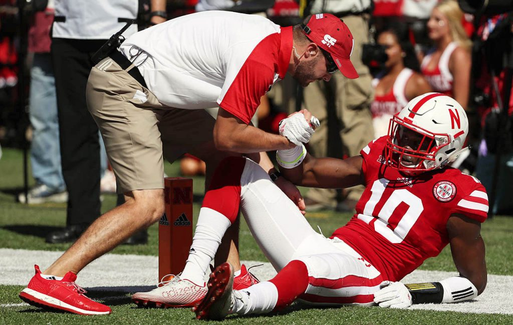 A Nebraska trainer gives a hand up to Cornhusker cornerback Joshua Kalu against Oregon at Memorial Stadium in Lincoln, Neb.