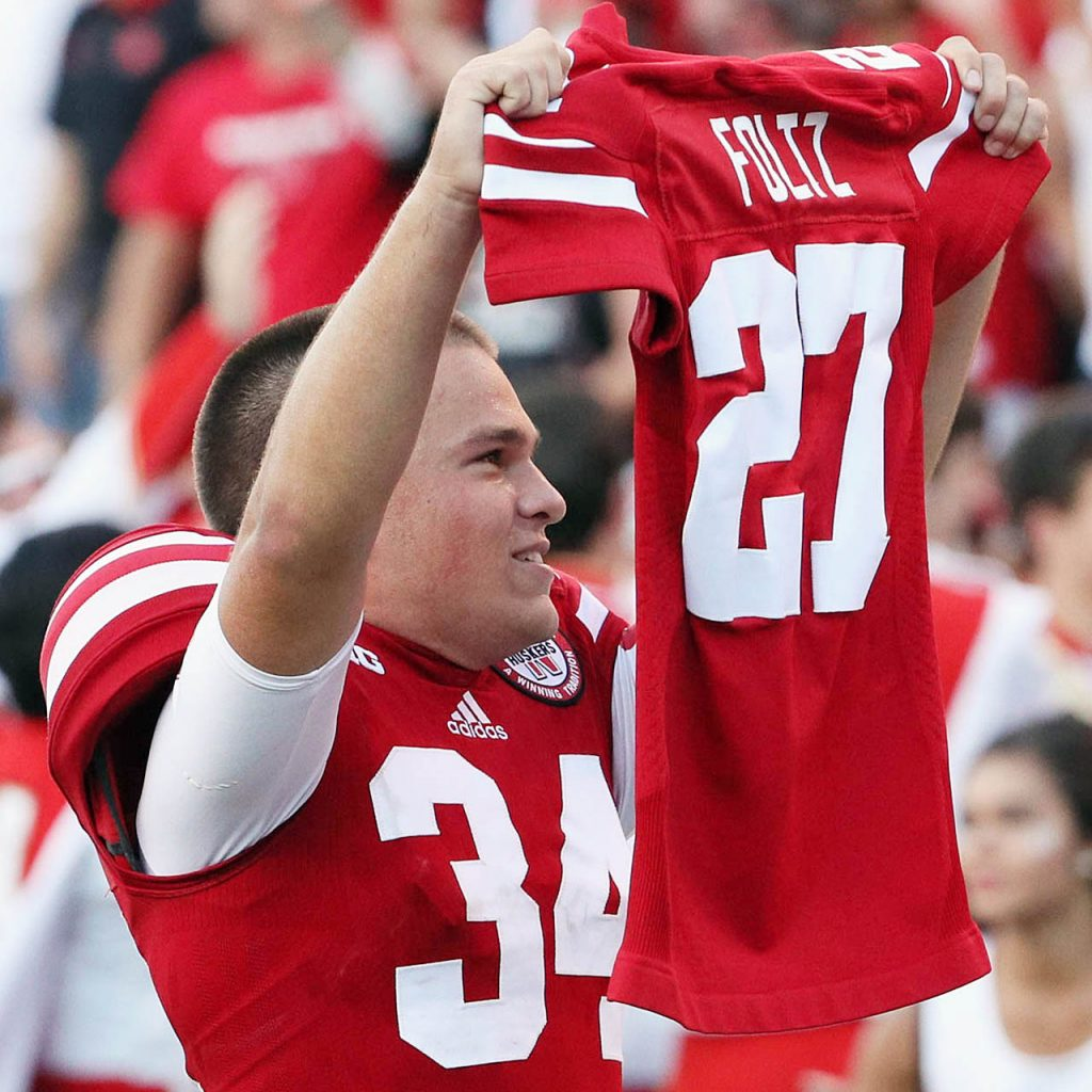 Nebraska place kicker Drew Brown holds up the late Sam Foltz jersey as the Cornhuskers celebrate their 35-32 come from behind victory against Oregon at Memorial Stadium.