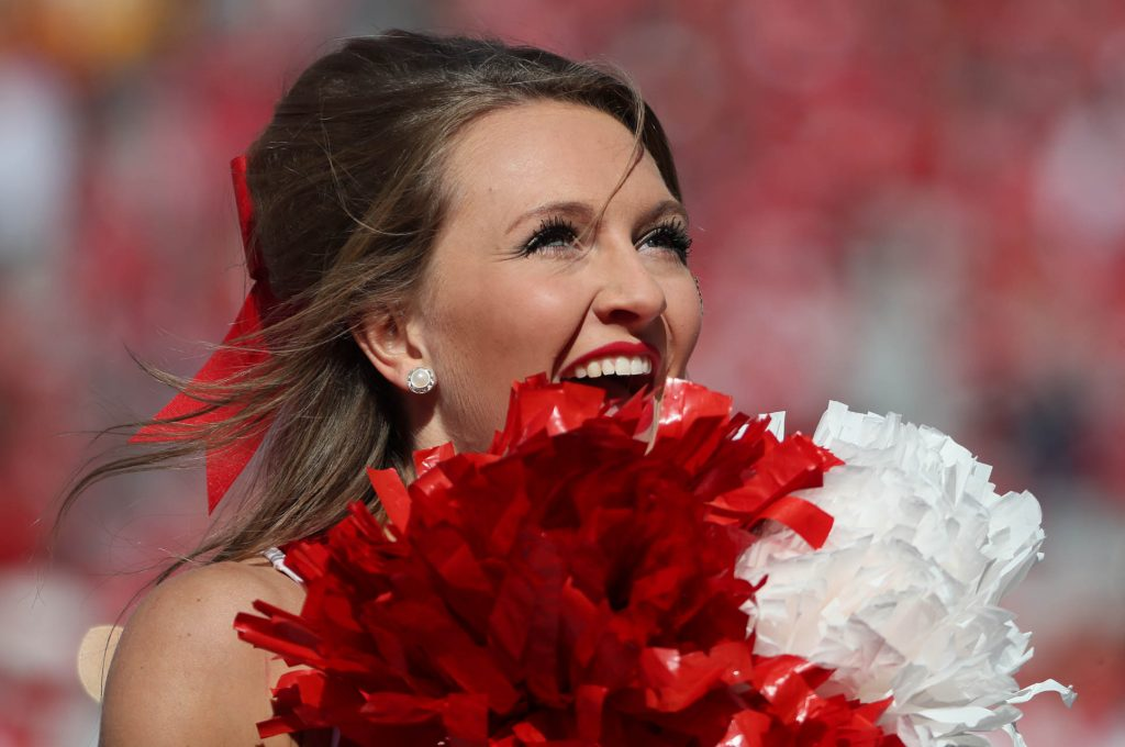 A Nebraska cheerleader looks up at fans while cheering during a NCAA football game at Memorial Stadium in Lincoln.