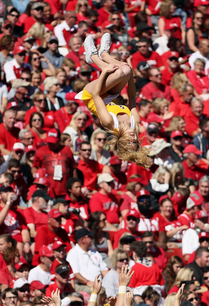 A Wyoming Cowboys cheerleader does back flips while performing during the Nebraska vs. Wyoming NCAA football game in Lincoln.
