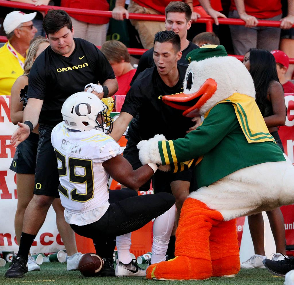 Oregon Ducks cheerleaders and the university mascot lend a helping hand to running back Kani Benoit after getting bumped out of bounds against Nebraska at Memorial Stadium in Lincoln, Neb.
