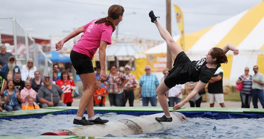 Katie Crecelius of Boston, Mass.,right, falls backwards off a Western Red Cedar log while competing with Sarah Perry in a Timber Tina's World Champion Lumberjills Show at the 2016 Nebraska State Fair.