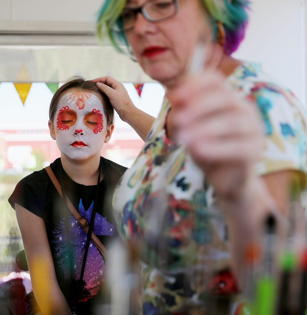 Dawn De Witt grabs a new paint brush while painting a fancy sugar skull on the face of Destiny Lucero of Grand Island at the 2016 Nebraska State Fair.