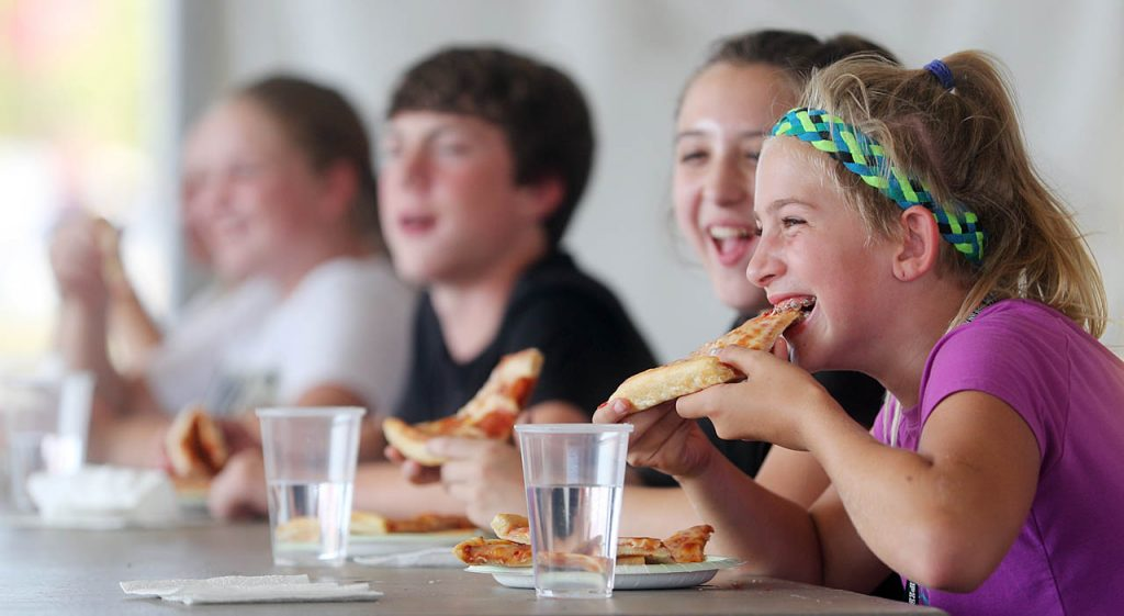Hadley Bockmann of Grand Island, right, shares a laugh while taking a bite of pizza in the 13-18 year-old Valentino's Pizza Eating Contest at the 2016 Nebraska State Fair Wednesday.