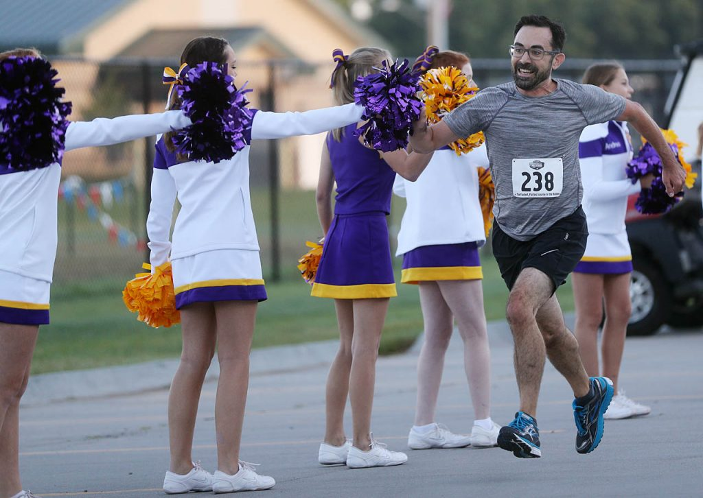 Tony Toth of Lincoln gives high fives to the Grand Island Senior High cheerleaders while approaching the finish line in a 5K run during the 2016 Nebraska State Fair Marathon. Toth is originally from Grand Island.