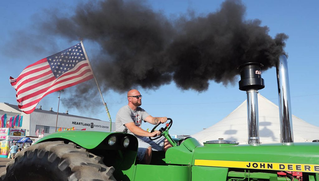 Smoke billows out of pipes on a John Deere tractor along the parade route during the 2016 Nebraska State Fair.
