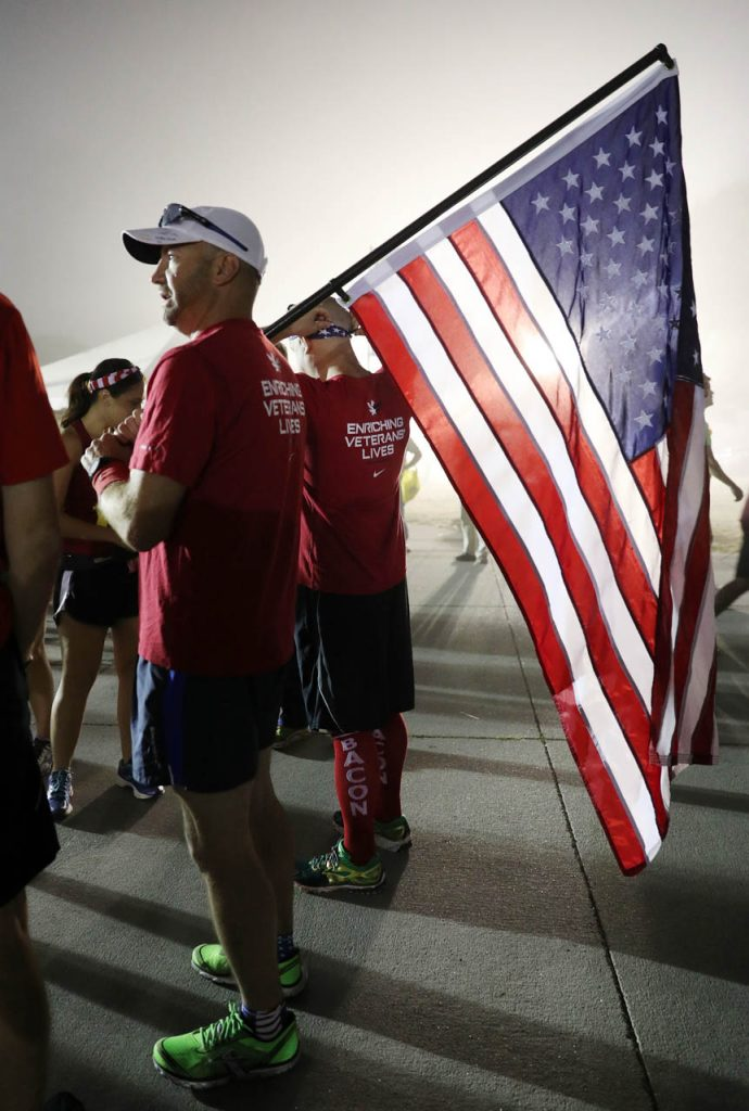 Dave Alder of Norfolk talks with his teammates while holding an American flag as a member of the Red, White and Blue team during the 2016 Nebraska State Fair Marathon on a foggy Saturday morning.