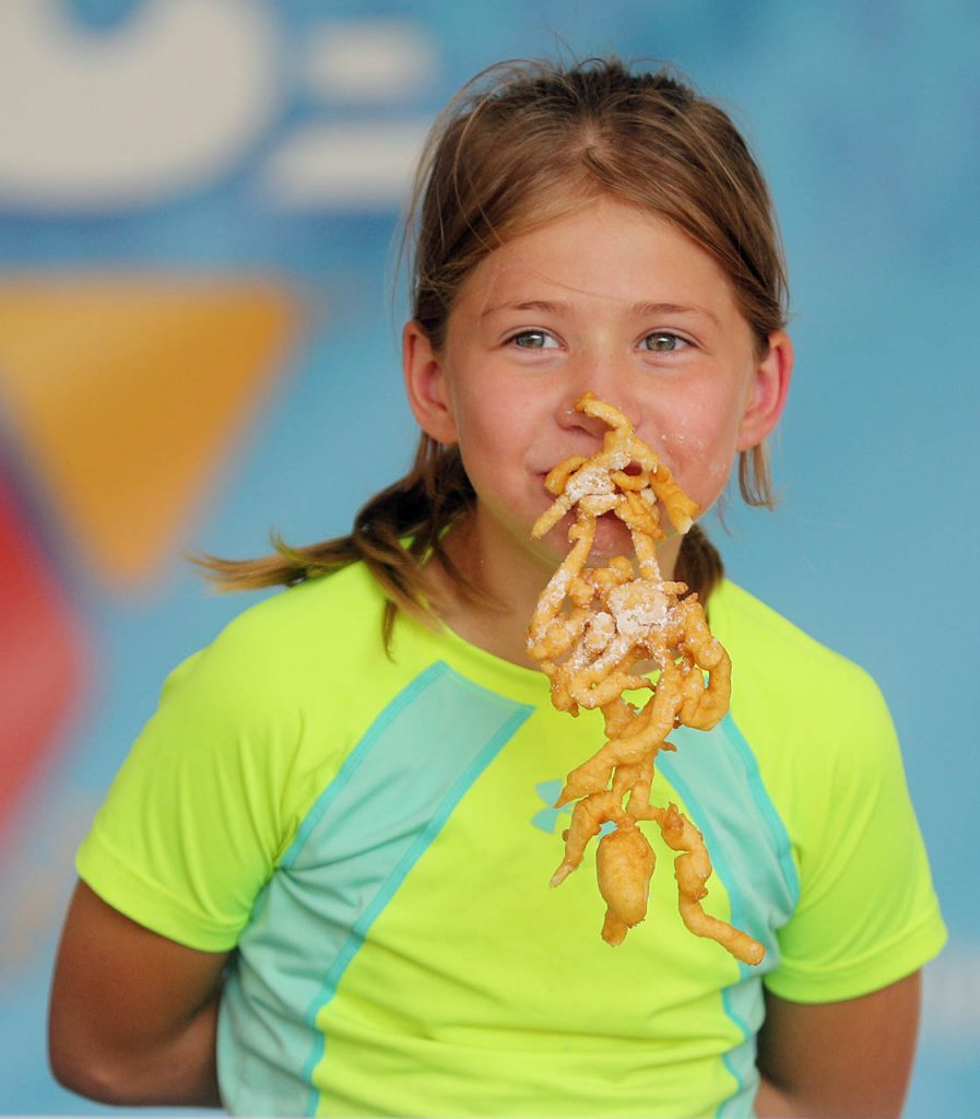 With her hands behind her back Matildesu Bristol of Grand Island competes in the King's funnel cake eating contest on the Family Fun Zone stage at the 2016 Nebraska State Fair.