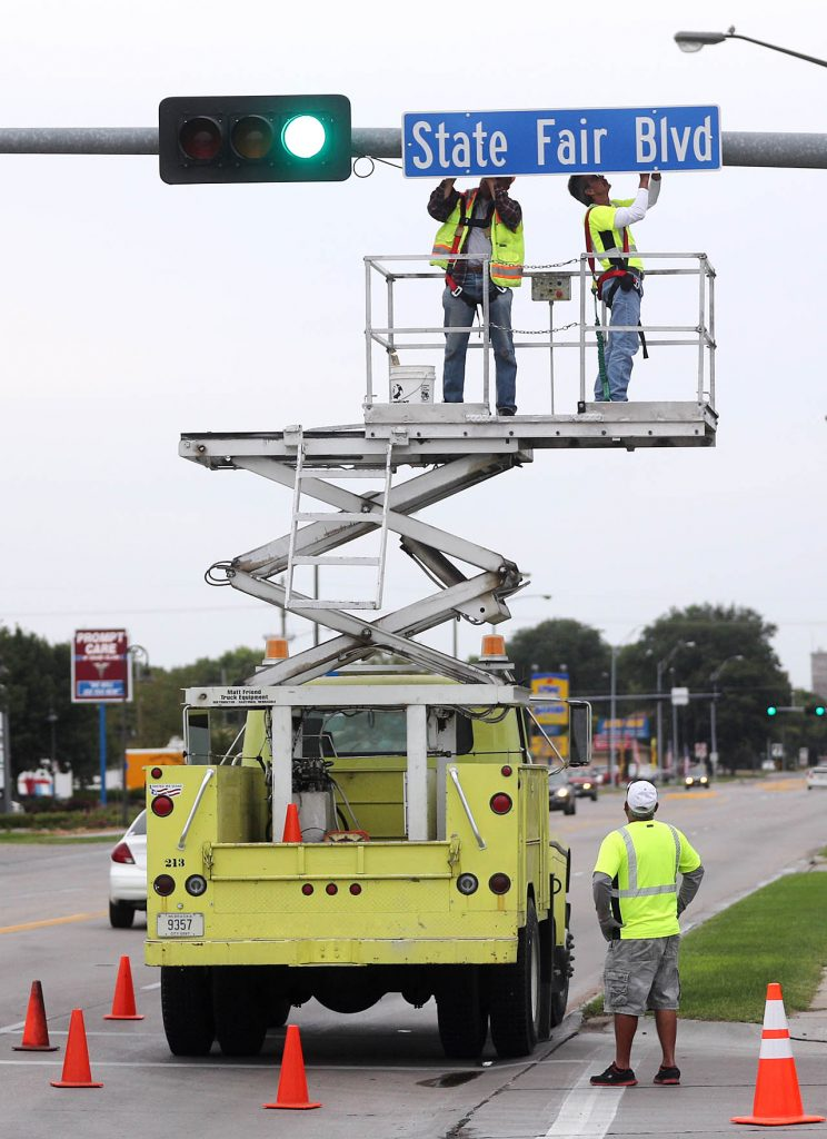 Public Works employees Harold Brei, left, and Kent Lentz work together to put up a new State Fair Blvd. street sign on S. Locust St. the morning before the opening of the 2016 Nebraska State Fair.