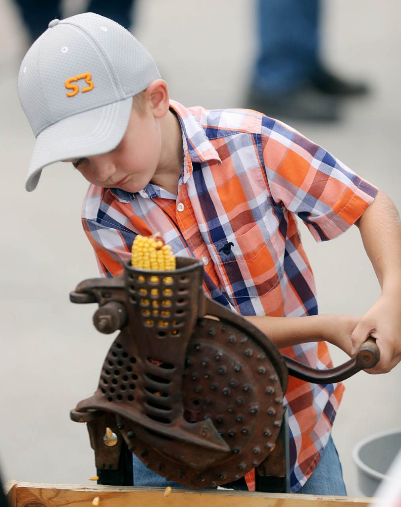Jake Hoffschneider of Wacko, uses both hands to turn the crank on a hand-corn Sheller at the 2016 Nebraska State Fair.