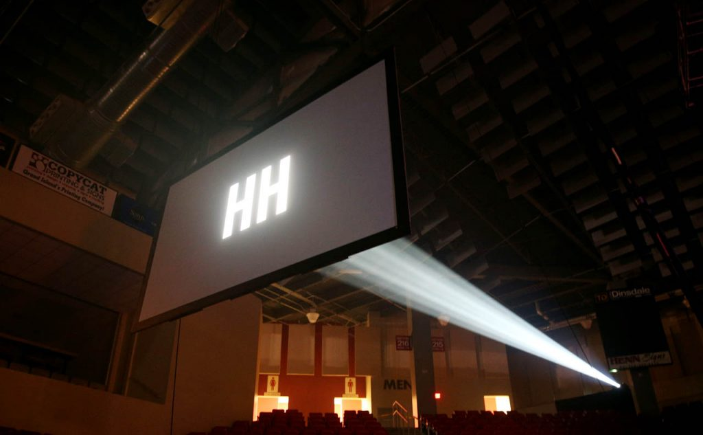 Hannah Huston's initials appear in lights shines on a silver screen prior to her concert at the Heartland Event Center.