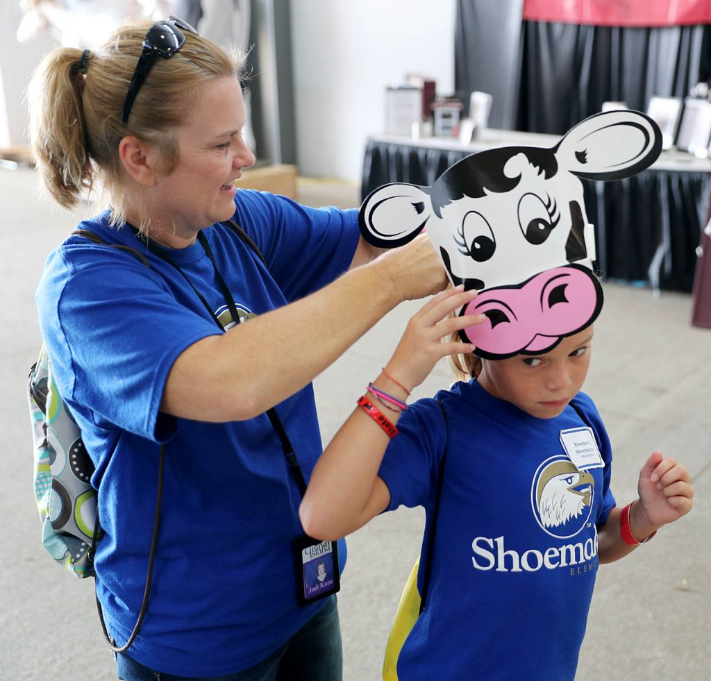 Para professional Jodi Kova, left, helps Shoemaker Elementary School third-grader Brooke Starman put on a cow hat during Nebraska's largest classroom day at the 2016 Nebraska State Fair Tuesday.