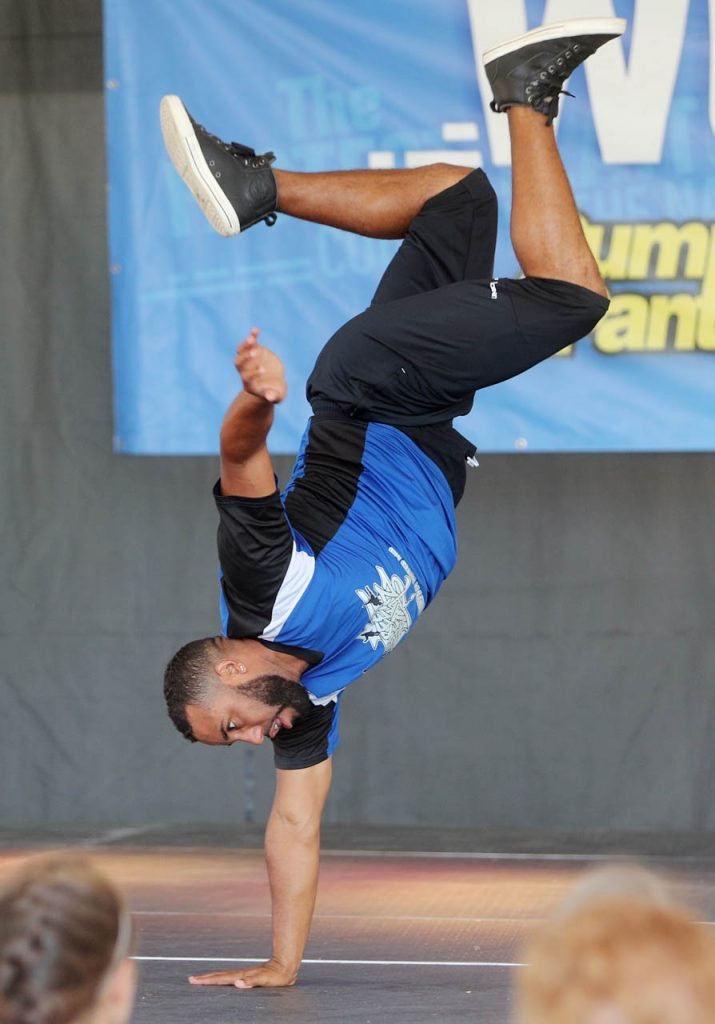 Street Breakz performer Anthony Sicardo of Orlando, Fla. balances on one hand while break dancing on stage under the Family Fun Zone tent at the 2016 Nebraska State Fair.