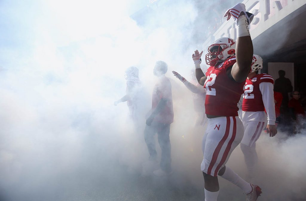 Nebraska's Devine Ozigbo walks through fog onto the field with his teammates at Memorial Stadium in Lincoln.