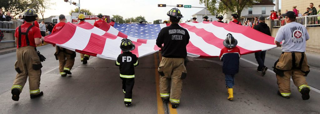 Grand Island firefighters and some of their children carry an American flag during the 2016 Harvest of Harmony Parade.