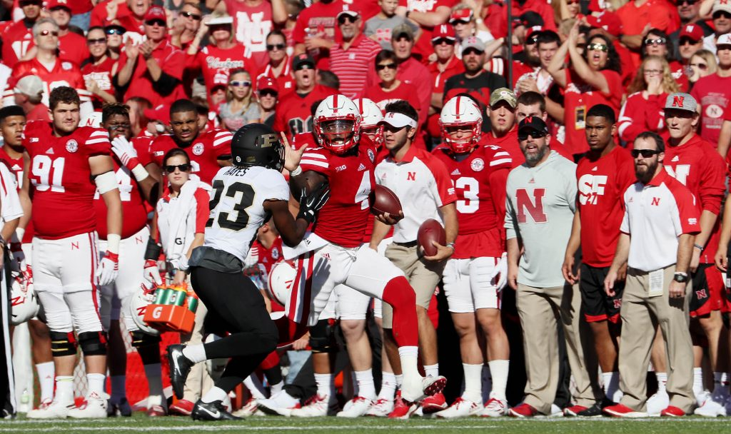 Nebraska quarterback Tommy Armstrong Jr. gives a stiff arm to Purdue cornerback Jack Wegher while running down the Husker sideline at Memorial Stadium in Lincoln.