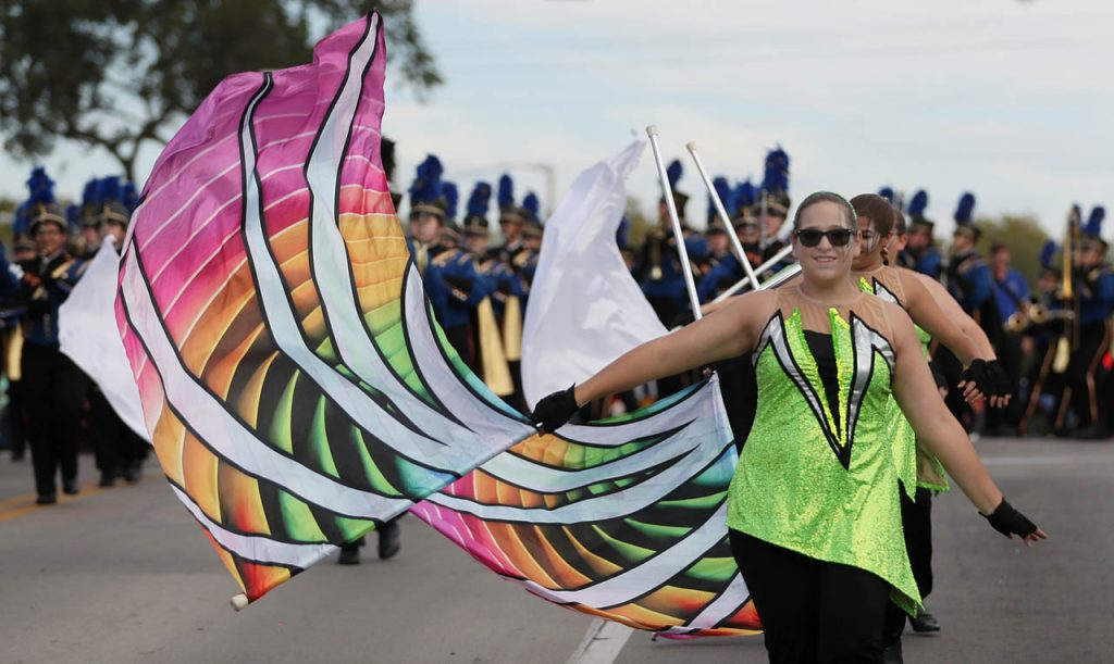 A North Platte Bulldog Marching Band flag line member leads a group of bandmates during the 2016 Harvest of Harmony Parade.
