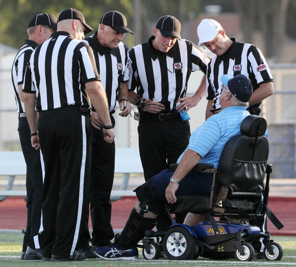Grand Island Central Catholic High School head football coach Bob Fuller talks to officials from his wheelchair prior to kickoff against Columbus Scotus at Memorial Stadium.