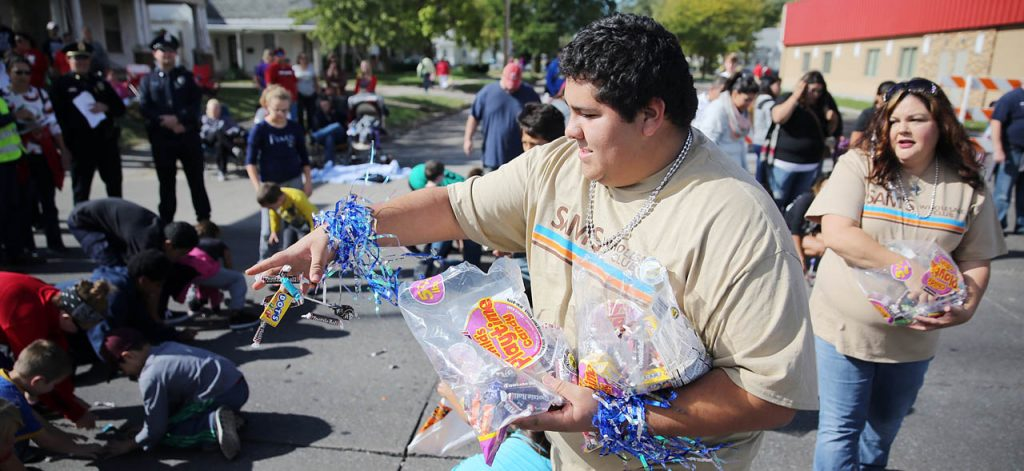 Julian Perez with Sam's Club in Grand Island, Neb. tosses candy to children along the 2016 Harvest of Harmony Parade route.