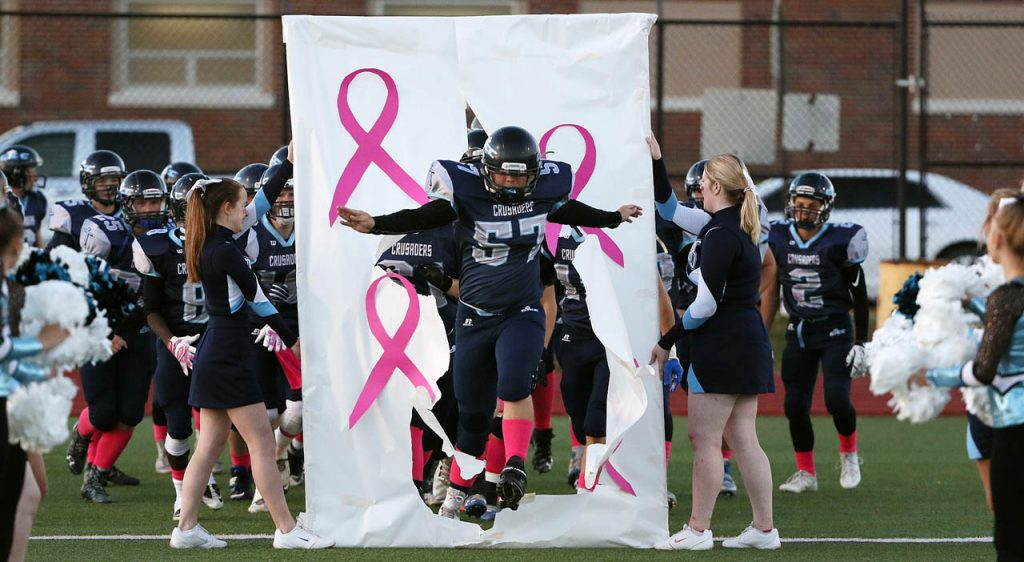 Central Catholic senior Aric Montgomery jumps through a cancer awareness banner held by Crusaders cheerleaders prior to kickoff against Lakeview at Memorial Stadium Friday night. (Independent/Andrew Carpenean)